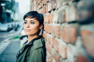 Half length of young handsome caucasian brown straight hair woman posing leaning against a wall, looking straight, pensive - serious, thoughtful concept
