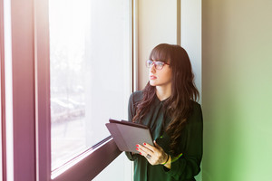 Half length of young handsome caucasian businesswoman near a window holding a tablet, looking down and tapping the screen - business, working, job concept