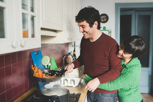 Half length of young handsome caucasian man and woman couple cooking together, she is hugging him form back and he is tossing a pan with vegetables - cooking, food, love concept