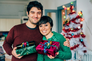 Half length of young handsome caucasian man and woman couple holding one gift each, looking at camera, hugging and smiling - christmas, happiness, love concept