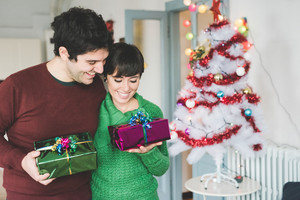 Half length of young handsome caucasian man and woman couple holding one gift each, looking downward, hugging and smiling - christmas, happiness, love concept