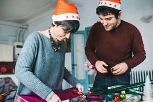 Half length of young handsome caucasian man and woman couple wrapping christmas present with wrapping paper and ribbon, both looking downward - christmas, couple, holiday concept