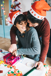 Half length of young handsome caucasian man and woman couple wrapping christmas present with wrapping paper and ribbon he is hugging her from back, smiling - christmas, couple, holiday concept