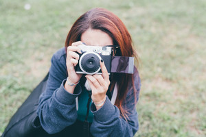 Half length of young handsome caucasian reddish straight hair woman holding an instant camera, taking a photo, looking in camera, smiling - photography, artist, creative concept