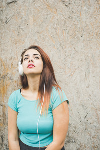Half length of young handsome caucasian reddish straight hair woman leaning against a wall listening music with headphones, looking upward, pensive - thinking future, thoughtful concept