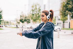 Half length of young handsome caucasian reddish straight hair woman listening music with headphones and smartphone handhold, overlooking left, dancing outdoor in the city