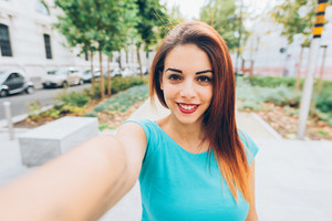 Half length of young handsome caucasian reddish straight hair woman taking a selfie, looking in camera, smiling - vanity, social network concept