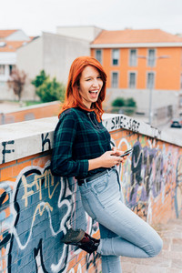 Half length of young handsome caucasian redhead straight hair woman leaning against a brick wall, looking in camera smiling, smart phone hand hold - youth, carefree concept