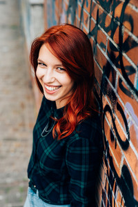 Half length of young handsome caucasian redhead straight hair woman leaning against a brick wall, looking in camera smiling, wearing checked blue and green shirt and jeans - youth, carefree concept