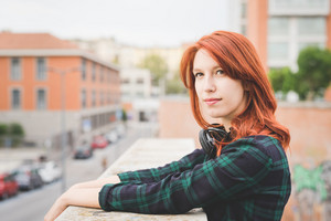 Half length of young handsome caucasian redhead straight hair woman leaning on a handrail, overlooking left, serene, headphones around her neck - carefree, youth concept