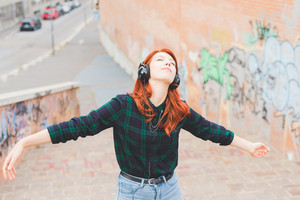 Half length of young handsome caucasian redhead straight hair woman listening music with headphones, feeling free with eyes closed and arms wide open - freedom, music, carefree concept