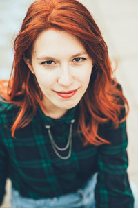 Half length of young handsome caucasian redhead straight hair woman looking in camera smiling, wearing checked blue and green shirt - youth, carefree concept