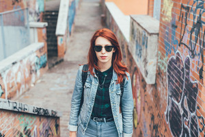 Half length of young handsome caucasian redhead straight hair woman posing on a staircase in the city, wearing sunglasses, looking in camera pensive - serious, thoughtful concept