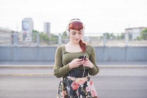 half length of young handsome caucasian redhead woman listening music with smartphone and headphones, looking downward, tapping the screen - relaxing, music concept - wearing green shirt, floral skirt