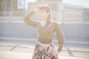 half length of young handsome caucasian redhead woman posing in the street, overlooking right, one hand on her hips, the other touching her hair, backlight - wearing green shirt and floral skirt