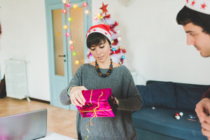 half length of young handsome caucasian woman wrapping christmas present with wrapping paper and ribbon - christmas, couple, holiday concept