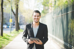 Half length of young handsome italian boy walking through the city using a tablet handhold connected online looking in camera smiling - technology, social network concept
