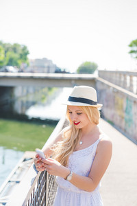 Half length of young handsome long blonde straight hair caucasian woman leaning on a handrail, using smartphone, looking downward the screen smiling - technology, communication, social network concept