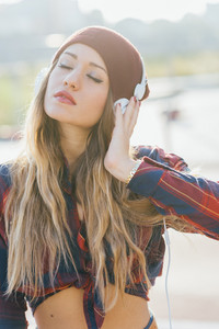 Half length of young handsome long straight hair woman listening music with headphones in back light, eyes closed pensive - music, technology, thinking future concept