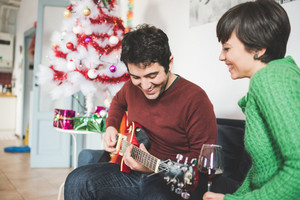 Half length of young handsome man and woman couple sitting on the sofa, he is playing guitar, she is looking at him, laughing - music, christmas, relax concept