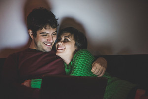Half length of young handsome man and woman couple sitting on the sofa using computer, hugging and smiling - focus on the man - technology, christmas, social network concept