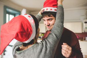 Half length of young handsome man and woman couple wearing Santa Claus hat indoor in their apartment, looking one in the other's eyes, smiling - happiness, christmas concept