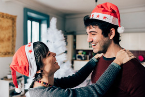 Half length of young handsome man and woman couple with Santa Claus hat embracing indoor in their apartment, looking one in the other's eyes, smiling - happiness, christmas concept