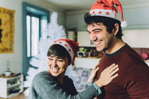 Half length of young handsome man and woman couple with Santa Claus hat embracing indoor in their apartment, overlooking smiling - happiness, christmas concept