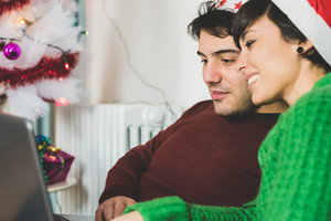 Half length of young handsome man and woman couple with santa claus hat sitting on the sofa using computer, looking screen, smiling - focus on the man - technology, christmas, social network concept