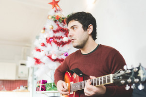 Half length of young handsome man sitting on the sofa, playing guitar - music, christmas, relax concept
