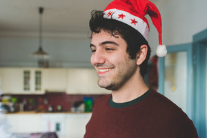 Half length of young handsome man wearing Santa Claus hat indoor in their apartment, smiling - happiness, christmas concept