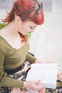 Half length of young handsome reddish pin up italian girl looking downward reading a book - culture, relax, break concept