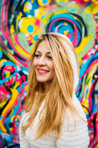 Half length portrait of young beautiful caucasian blonde hair woman leaning on a colorful wall, overlooking smilng - carefree, serene, thoughtless concept