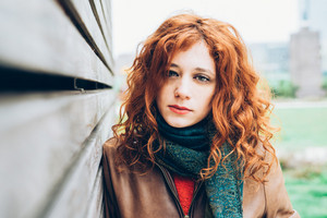 Half length portrait of young beautiful caucasian redhead woman looking in camera, pensive - intense, thoughtful, determination concept