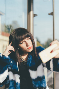 Half length portrait of young beautiful eastern woman sitting at the bus stop taking a selfie with smart phone hand hold - commuter, vanity, technology concept