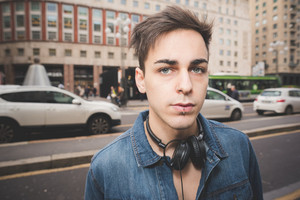Half length portrait of young handsome alternative dark model man in town with headphones around his neck, looking in camera, pensive - thoughful, serious concept