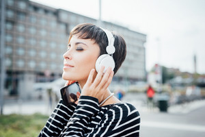 Half length portrait of young handsome caucasian brown straight hair woman listening music with headphones and smartphone handheld, overlooking left, smiling - music, relax, technology concept
