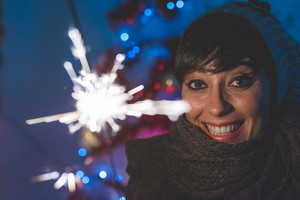 Half length portrait of young handsome caucasian short brown hair woman celebrating holding a sparkler, looking at camera, smiling - celebrating, new year eve, happiness