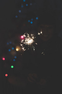 Half length portrait of young handsome caucasian short brown hair woman celebrating holding a sparkler, looking the flame, smiling - celebrating, new year eve, happiness
