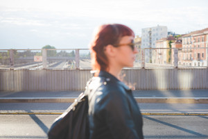 half length profile of a young handsome caucasian redhead woman walking in the city, overlooking left, pensive - seriousness concept - backlight - wearing a leather jacket - focus on the background