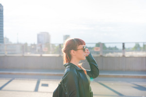 half length profile of a young handsome caucasian redhead woman walking in the city, overlooking left, pensive - seriousness concept - backlight - wearing a leather jacket