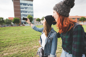 Half length profile of two young handsome caucasian blonde and redhead hair women walking in the city, holding smartphone, taking selfie, smiling - social network, communication, vanity concept