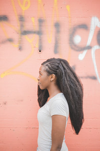 Half length profile of young beautiful long brown hair black woman standing on orange wall, overlooking smiling - happiness, thoughtless concept