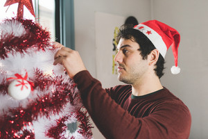 Half length profile of young handsome caucasian brown man with Santa Claus hat decorating christmas tree, looking downward - christmas, holiday concept