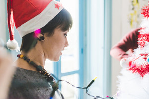 Half length profile of young handsome caucasian brown short hair woman with Santa Claus hat decorating christmas tree, looking downward - christmas, holiday concept