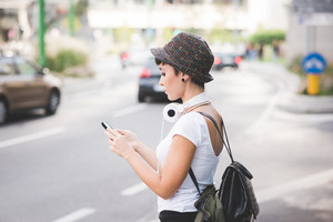 Half length profile of young handsome caucasian brown straight hair woman walking in the city holding a smartphone, looking down the screen - technology, communication, social network concept