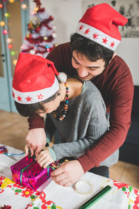 Half length profile of young handsome caucasian man and woman couple wrapping christmas present with wrapping paper and ribbon he is hugging her from back, smiling - christmas, couple, holiday concept