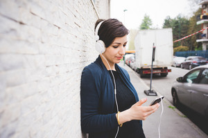 Half length profile portrait of young handsome caucasian brown hair woman leaning against a wall, listening music with headphones, eyes closed - serene, enjoying, music concept