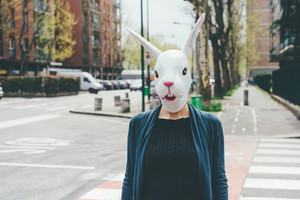 Half length woman wearing rabbit mask outdoor in the city - halloween, dreamlike, strange concept