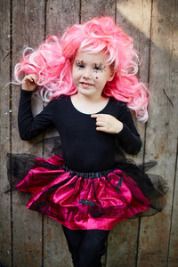 Halloween girl in pink wig looking at camera with smile
